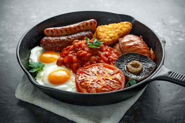 97035618 - full english breakfast with bacon, sausage, fried egg, baked beans, hash browns and mushrooms in rustic skillet, pan.