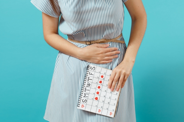 105169710 - cropped illness woman in blue dress holding periods calendar for checking menstruation days put hand on abdomen isolated on blue background. medical, healthcare, gynecological concept. copy space