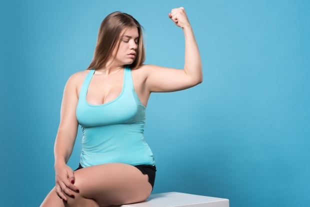 68510086 - i see progress. young pretty plump lady sitting and looking at her biceps isolated on blue background.
