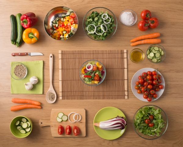 39363729 - creative vegetarian cooking at home concept with fresh healthy vegetables chopped, salads and kitchen wooden utensils, top view with copy space