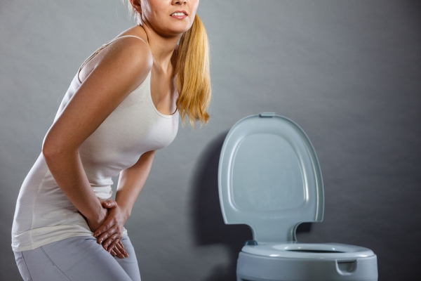 78694552 - sick woman with hands holding pressing her crotch lower abdomen in front of toilet bowl. medical problems, incontinence, health care concept