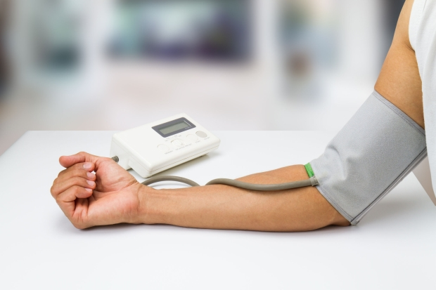 78620398 - man measureing his blood pressure on white desk at home on blurred living room