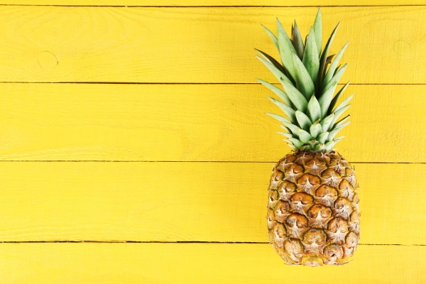 51102174 - ripe pineapple on a yellow wooden background