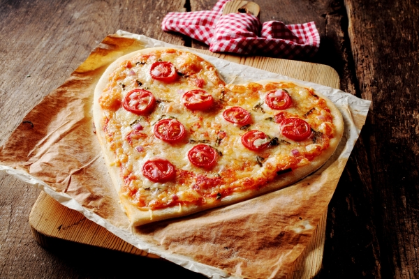 44952168 - baked heart-shaped homemade pizza topped with mozzarella and tomato slices, on parchment paper on a cutting board near a checkered red and white kitchen towel, on a rustic table, high-angle close-up