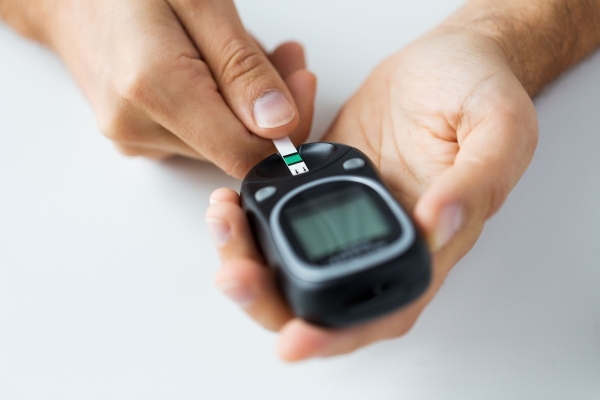 48221176 - medicine, diabetes, glycemia, health care and people concept - close up of man checking blood sugar level by glucometer and test stripe at home