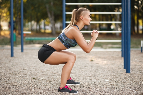 84403495 - deep squat. side view of young beautiful woman in sportswear and piercing doing squat  while standing on the sport ground in the park.
