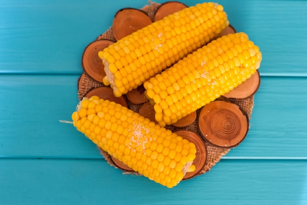 83864720 - boiled corn on a blue wood background