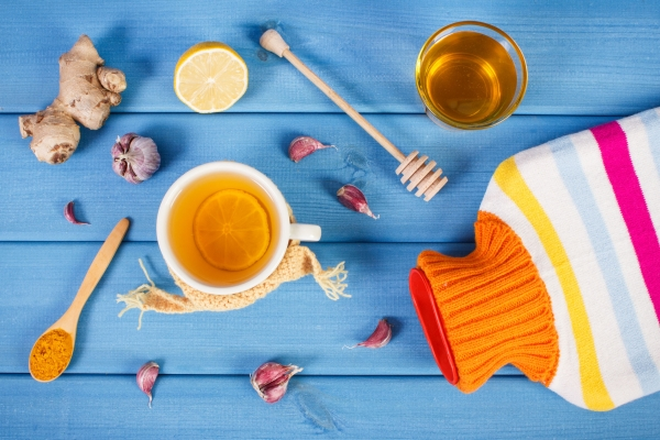 63897145 - hot water bottle, cup of tea with lemon and ingredients for preparation warming beverage for flu and cold, health care concept