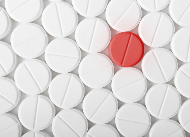 44972308 - top view of the heap of white medicine pills on white surface. one red medicine tablet is as a concept of a vaccine.