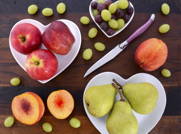 44256512 - assortment of fruit, including apples, pears, nectarines and grapes, on white heart shape plates on rustic wood table, overhead.