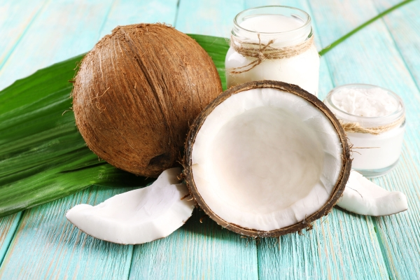 43113466 - fresh coconut oil in glassware and green leaf on color wooden table background