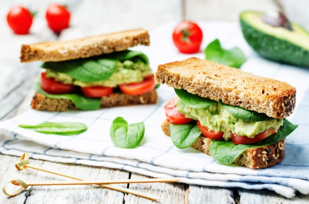 55671821 - smashed avocado spinach tomato grilled rye sandwich. toning. selective focus