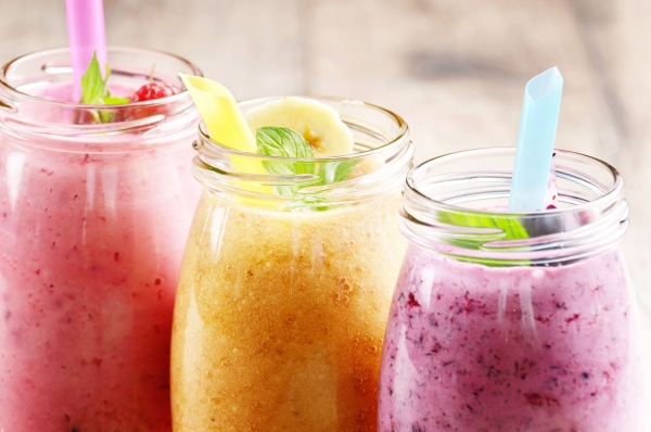 43663582 - assorted fruit shakes on white table. smoothie concept