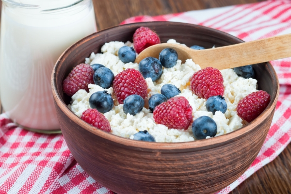44340901 - cottage cheese with raspberries and blueberries in brown clay bowl and wooden spoon on red checkered towel