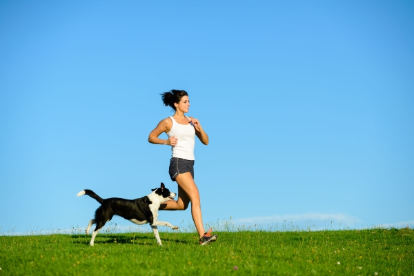 38786391 - woman and dog running and exercising outdoor at grass field on summer or spring. happy female athlete training with her pet.