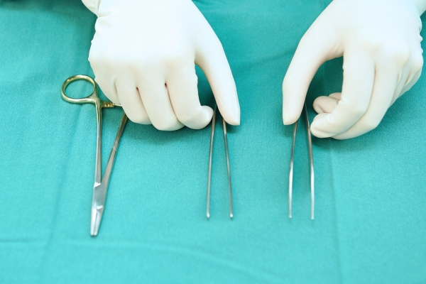 48439125 - detail shot of steralized surgery instruments with a hand grabbing a tool