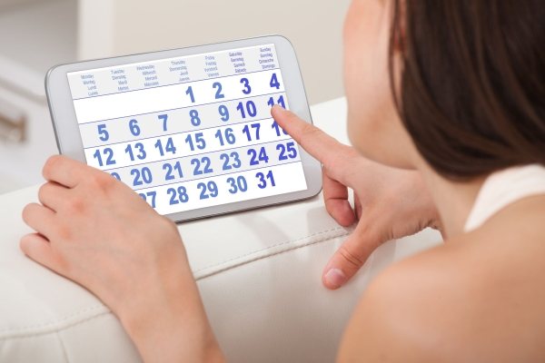 30786086 - cropped image of young woman using calendar on digital tablet at home