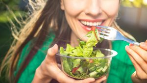Woman eating healthy salad, focus on fork with salad