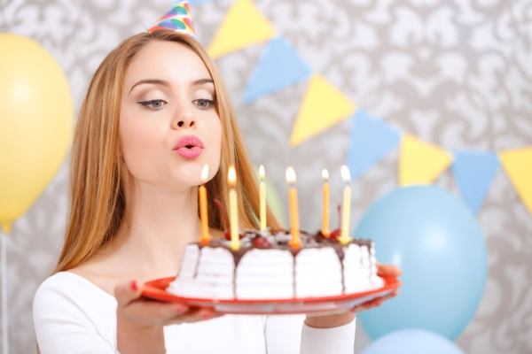 40178511 - portrait of a young beautiful blond girl wearing cone cap holding a red plate with birthday cake and blowing candles making a wish