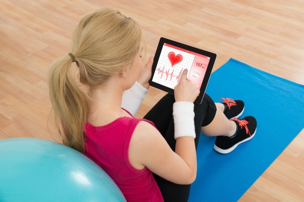 43082376 - young woman looking at heart pulse rate on digital tablet in living room