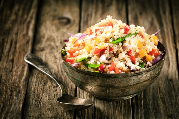 28234789 - healthy vegetarian quinoa recipe with colourful bell pepper, tomato, onion and fresh herbs in a rustic metal bowl on an old wooden kitchen counter