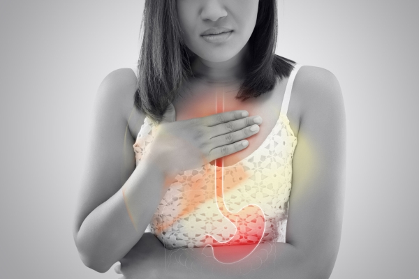 103148371 - woman suffering from acid reflux or heartburn against gray background / asian people with symptomatic indigestion or gastritis