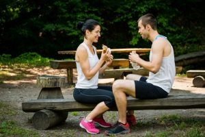 51640305 - young couple eating together after jogging outdoor in nature