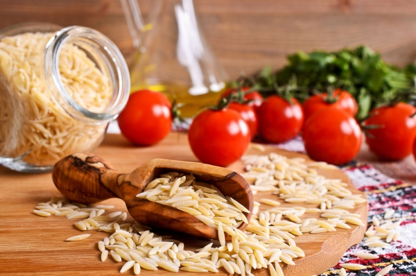 35551145 - pasta orzo in the form of rice grains in a wooden scoop