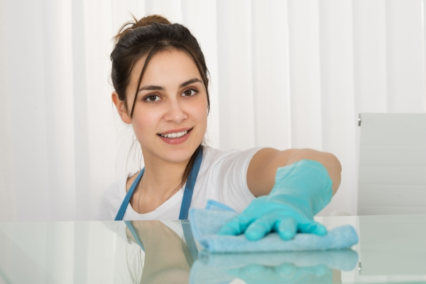 53332504 - close-up of happy female janitor cleaning desk with rag