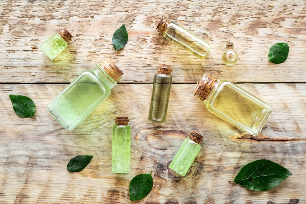 89275775 - skin care products with tea tree oil in bottles on rustic wooden background top view pattern.