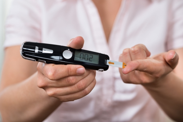 42192821 - close-up of woman hands testing high blood sugar with glucometer