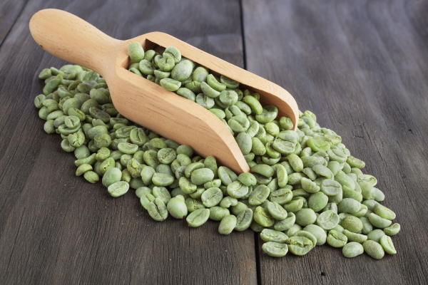 44632812 - green coffee beans in wooden scoop on vintage wooden surface
