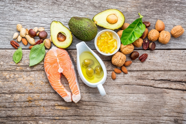 87324242 - selection food sources of omega 3 and unsaturated fats. superfood high vitamin e and dietary fiber for healthy food. almond,pecan,hazelnuts,walnuts,olive oil,fish oil and salmon on wooden background.