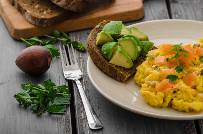 Scrambled eggs with smoked salmon and whole wheat toast with avocado and lemon