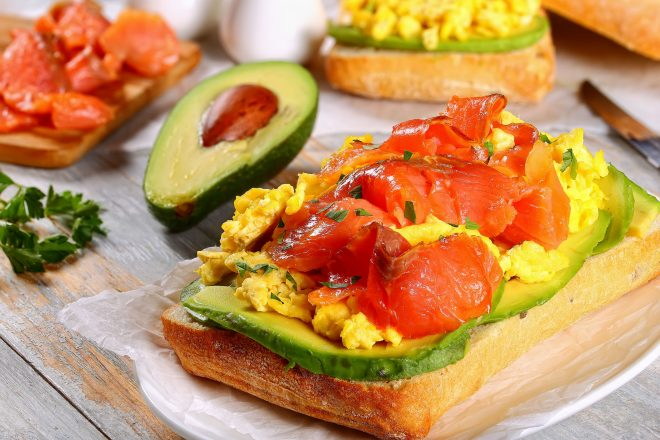 smoked salmon avocado scrambled egg italian ciabatta delicious sandwich sprinkled with parsley on white paper on oval dish with ingredients on background, healthy recipe, view from above, close-up