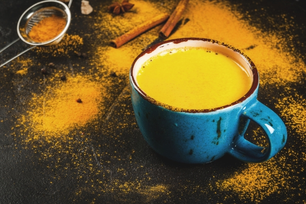 74709500 - traditional indian drink turmeric milk is golden milk with cinnamon, cloves, pepper and turmeric. on a concrete table, with spices on the background. in a large cup, copy space, toned