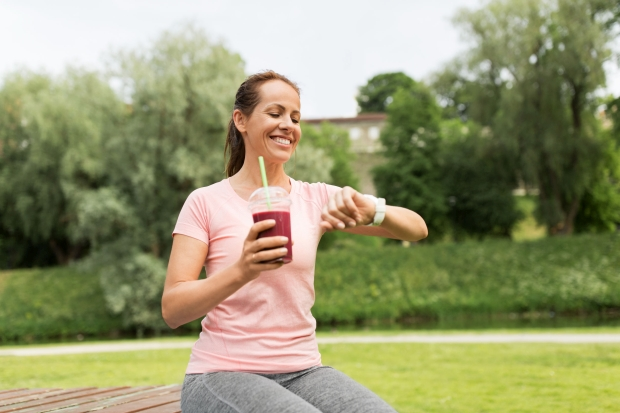 fitness, sport and healthy lifestyle concept - woman with smoothie or shake in plastic cup looking at smart watch in park