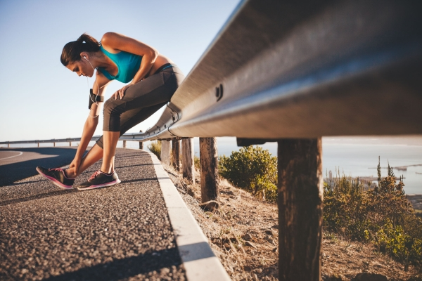 42096422 - sports woman stretching her leg after running outdoors. female athlete taking break after running training sitting on highway guardrail.