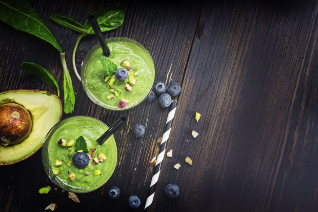 95336819 - smoothie with green spinach, pistachio and avokado on dark wooden board. well being and weight loss concept.