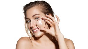 Beautiful woman with magnifier near her face. Getting rid of wrinkles concept. Clean healthy skin and cosmetology concept. Image for cosmetology clinic advertising.