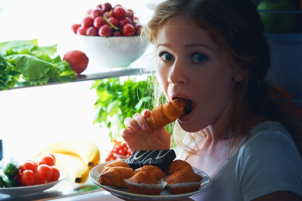 41607652 - woman eats sweets at night to sneak in a refrigerator