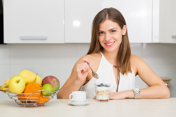 43874939 - beautiful woman having coffee, fruits and oatmeal for breakfast