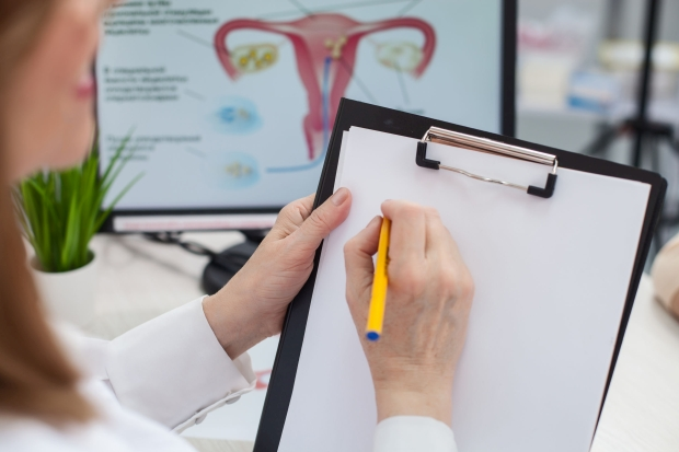 Close up of cheerful female gynecologist is writing a prescription. She is sitting at the desk and holding a folder of papers. The woman is smiling