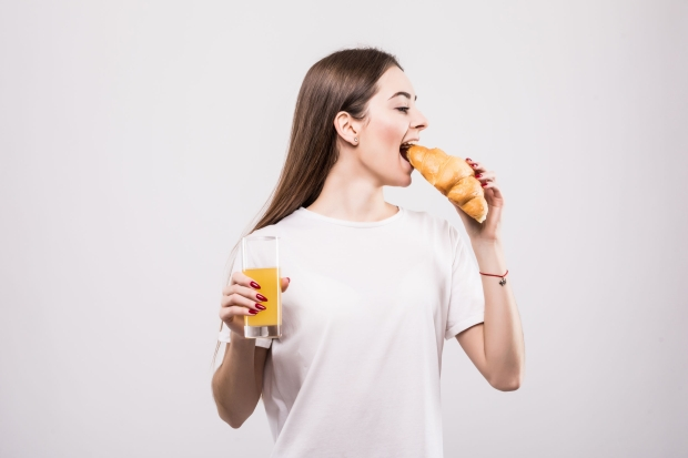 Young woman eating croissant with orange juice. Modern woman eating fast food.