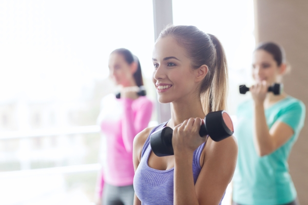 41728754 - fitness, sport, training and lifestyle concept - group of happy women with dumbbells flexing muscles in gym