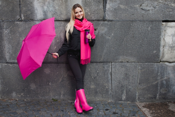 Beautiful young and happy blond woman with colorful umbrella on the street. The concept of positivity and optimism. Girl in a bright pink scarf, rubber boots and umbrella on the background of gray stone wall