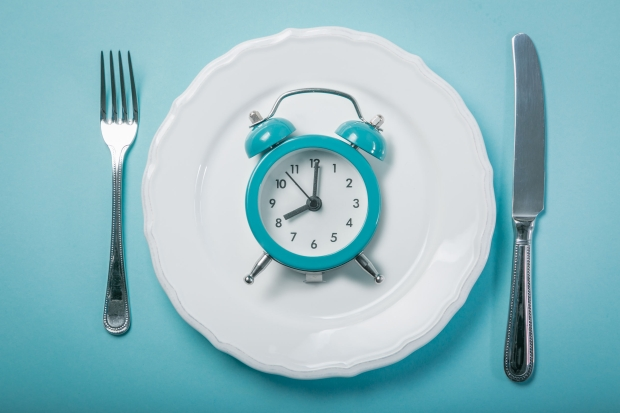 97349069 - intermittent fastin concept - empty plate on blue background