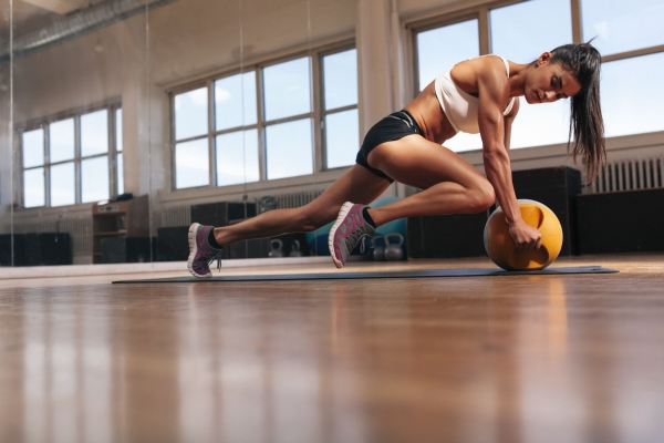 Woman doing intense core exercise on fitness mat. Muscular young woman doing workout at gym.