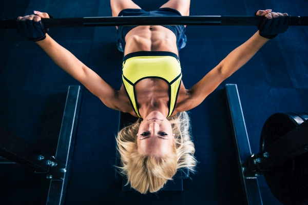 Fitness woman workout with barbell on bench in gym