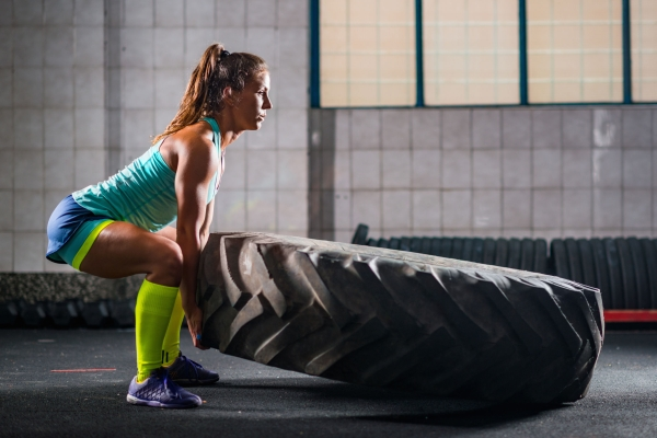83350481 - woman athlete exercising with tire